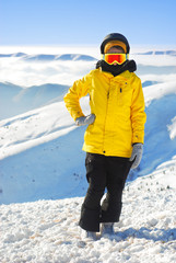girl in snowboard equipment against the backdrop of snow-capped