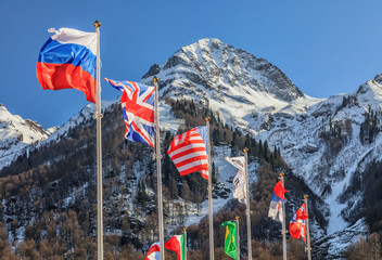 National flags of Russia, Great Britain, USA and other countries waving in the wind at winter on mountain peak background