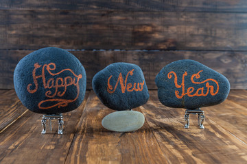 Happy New Year.  Hand lettering written on pebbles placed on tiny chairs on wooden table