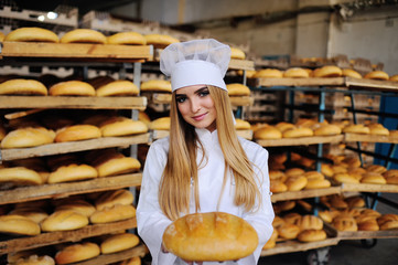 pretty young girl in a white uniform and cap on background bakery holding a loaf of bread