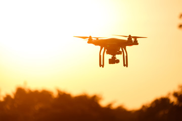 Drone silhouette flying in the sunset light beautiful