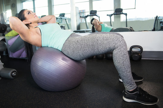 Healthy woman doing situps on exercise ball during gym workout