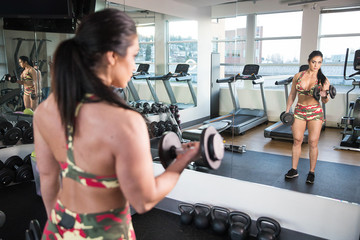 beautiful woman in camo working out in front of mirror at gym