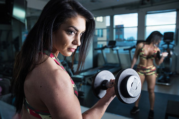 Strong bodybuilder woman curling with barbell in front of mirror