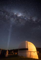 Woman standing next to an observatory under the Milky Way