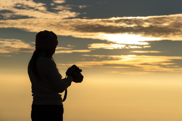 Silhouette of photographer taking picture of landscape during sunset, soft and select focus