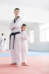 Young instructor and boy in taekowndo gymnasium