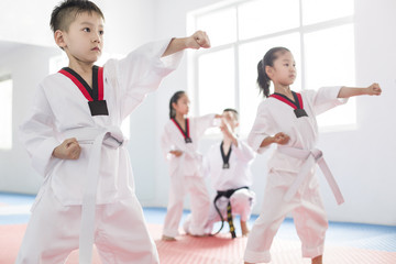 Young instructor teaching children taekwondo in studio
