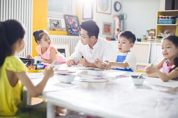 Little children painting in art class with teacher