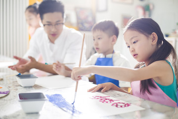 Little children painting in art class with teacher