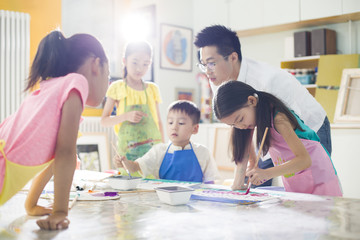 Children painting in the art class with teacher