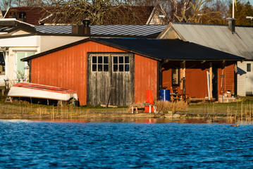 Red wooden boathouse as seen from the sea. Doors closed and small rowboat on land outside. Calm and sunny weather.