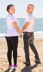 Mature couple on the beach holding hands and looking back