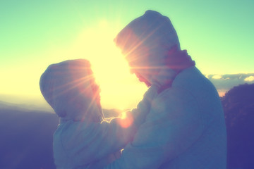 Silhouette of couples happy at scenic mountain fog and sun.