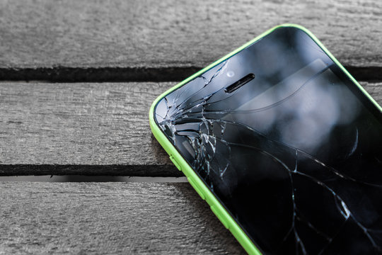 Broken screen glass of mobile smartphone on the wood table