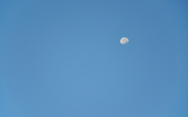 Day moon in blue sky