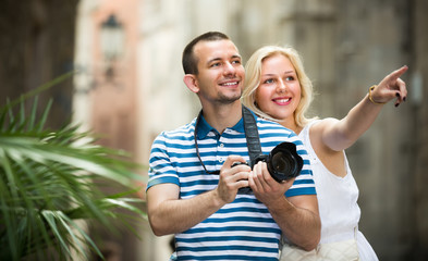 young couple taking pictures outdoors.
