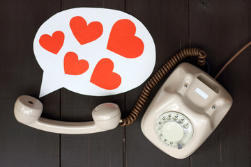 greetings on the day of lovers/ talking on the phone concept as a set of hearts flying out of the tube
