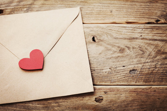 Envelope or letter and red heart on vintage wooden table for love message on Valentines Day in retro toning.