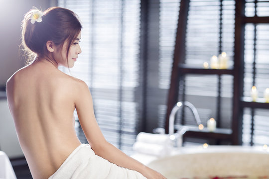 Shirtless beautiful young woman wrapped in towel