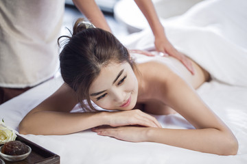Masseuse giving a back massage to a woman in a spa