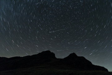 Star trails over the mountain hill