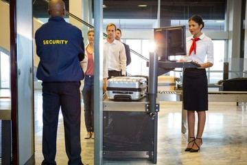 Airport security guard with passenger walking through scanner