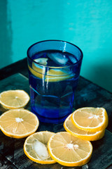 Sparkling water, soda or a gin and tonic in bright blue glass with lemon and ice.Concept for bar menu or detox  with water with lemon.