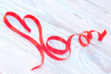 Happy Valentines Day. Red Ribbon Heart on a wooden background. Valentines Day concept