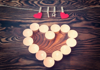 Valentine's day. Heart of candles. Red wooden hearts with pins and figures of FEB. 14 hanging on the rope on the brown wooden background