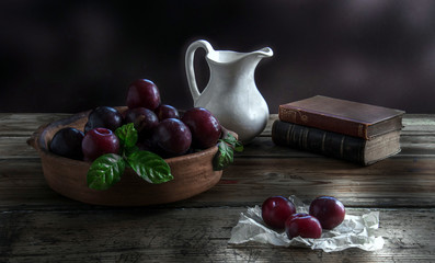 old books , white jug and fruits on a wooden table