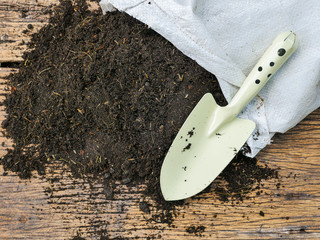 Organic soil with bag for planting on wood background