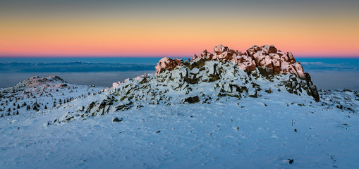 Amazing winter sunset - beautiful frozen landscape, jagged rocks and orange skies - tiny figures on a rocky outcrop