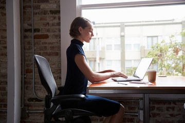 Businesswoman Sitting At Desk By Window Working On Laptop