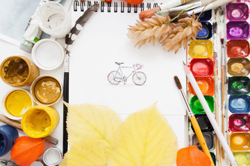 Pretty pictured bicycle on artist work flat lay. Top view on painter workplace with gouache and watercolor palette, paintbrushes and autumn yellow leaves. Fall inspiration concept