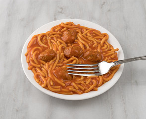 Plate of spaghetti and meatballs with fork on a gray marble table.