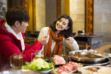 Young couple having dinner in hotpot restaurant