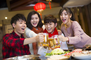 Young friends toast beer mugs in a restaurant