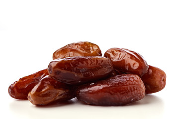 Close up of fresh brown dates against a white background