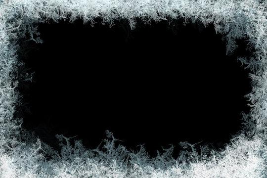 Frostwork. Decorative ice crystals frame on black matte background