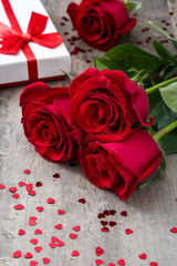 Gift box and red rose on wooden background.Valentines concept