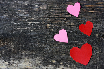 Wooden surface, and paper hearts.