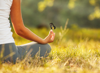 Young woman practicing morning meditation in nature at the park. Health lifestyle concept. Wall mural