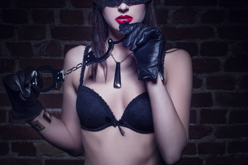 Sexy womanwith red lips holding handcuffs