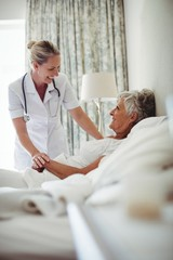 Female doctor interacting with senior patient