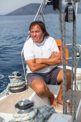 Mature man sits on his sail yacht. Vacation, sailing, travel.