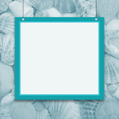 Turquoise hanging frame with white space on the background of sea shells.