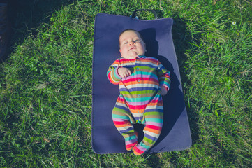 Little baby on a mat in the grass