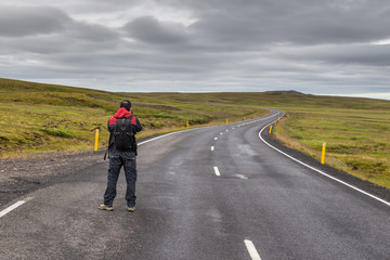 Man taking a picture of empty road on Iceland.