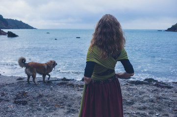 Young woman walking dog on beach